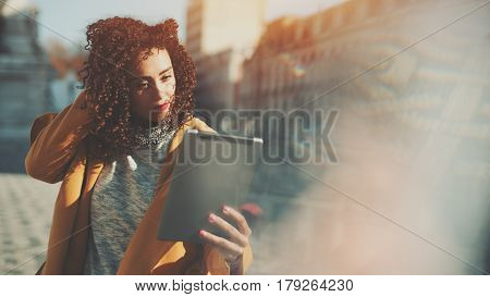 Beautiful curly woman in yellow fixing hair using camera of her digital tablet as mirror adult attractive lady making selfie on touch pad with copy space for your message or promotional content