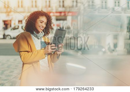 Beautiful smiling curly Brazilian woman in yellow coat having video call using digital tablet adult attractive lady making selfie on touch pad with copy space for your message or promotional content