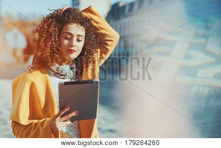 Attractive curly Brazilian woman in yellow coat and sweater making selfie using digital tablet adult beautiful smiling lady with touch pad standing on sunny street with copy space for your message