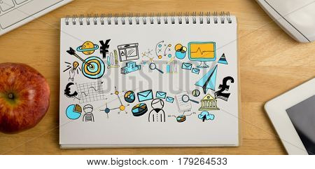 Digitally generated image of business computer icons against overhead of notepad and technology