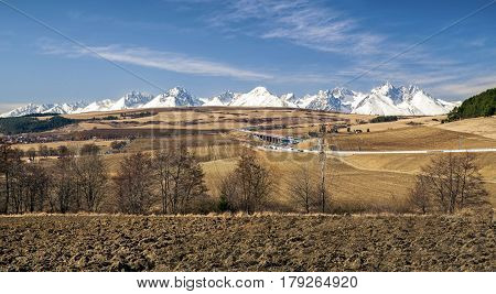 Snowy peaks of High Tatrs mountains and brown earth landscape. Higway D1 full of cars
