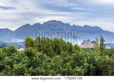 Spanish countryside with olive trees, typical Spanish village and the mountains in the background