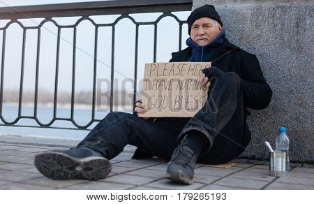 Please help me. Thoughtful male wearing dirty clothes holding poster in his hands, looking straight