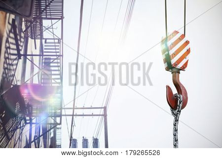 Studio Shoot of a crane lifting hook against electric cables and building exterior