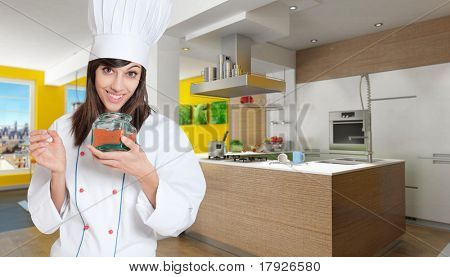 Young female chef in a kitchen interior with a glass jar with red chilly powder