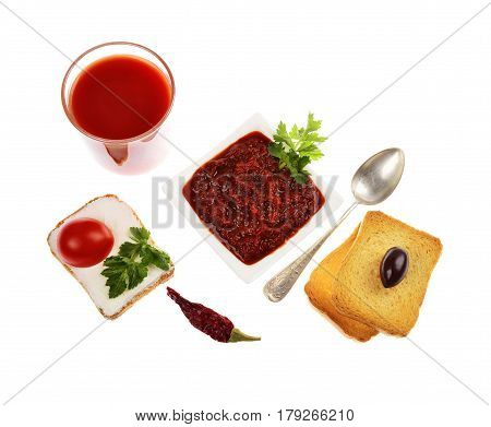 Homemade tomato chutney in a bowl of tomato juice in a glass isolated on white background