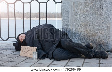 Feel depressed. Upset male putting poster and tin near himself, wearing dirty clothes while covering himself with warm jacket