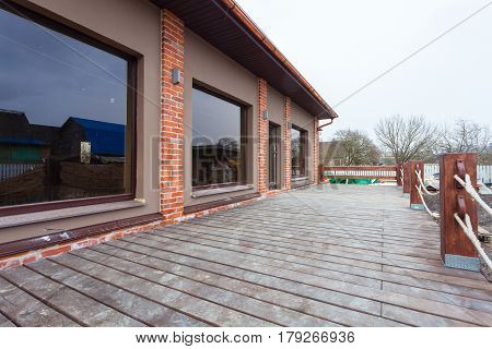 The modern house with big windows and with wide wooden terrace is under the remodeling renovation and construction