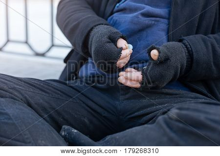 In process. Close up of male hands wearing gloves keeping coins being on the belly