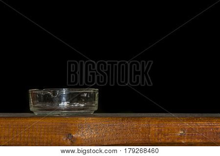 Ashtray on wooden table isolated on  black background