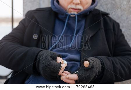 Feeling anxious. Serious bearded man wearing dark clothes, leaning on the wall while counting money