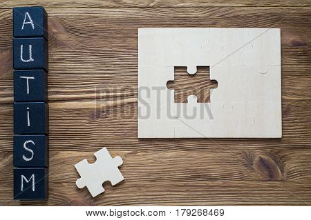 Puzzle pieces and black wooden cubes with word AUTISM on wooden background top view flat lay. Autism Spectrum Disorder (ASD). Autism awareness. Concept of autism word.