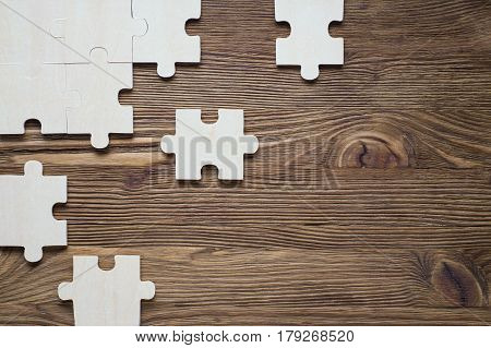Business concept with jigsaw puzzle on wooden background. Incomplete wooden puzzles on brown wooden desk top view flat lay. The concept of logical thinking conundrum. poster