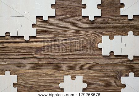 Incomplete wooden puzzles on brown wooden desk top view flat lay. Frame with puzzle. The concept of logical thinking business conundrum. Business concept with jigsaw puzzle on wooden background.