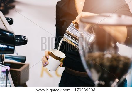 Woman Barista Adding Milk To Coffee