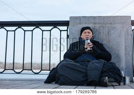Warm memories. Full length photo of wise man looking forward leaning on the column sitting in the street
