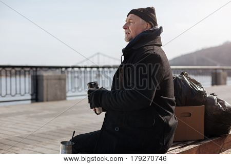 Look around. Very attentive old male wearing black coat holding thermos in both hands looking straight