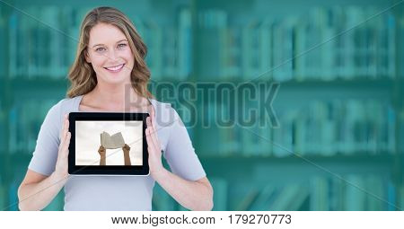 Digital composite of Woman with tablet showing hands with book against blurry bookshelf with teal overlay