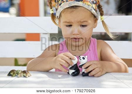 A girl playing with toy pandas at the table half-breed Asian mestizo