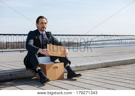Ask for help. Serious jobless male wearing costume holding box with paper between legs while sitting in semi position