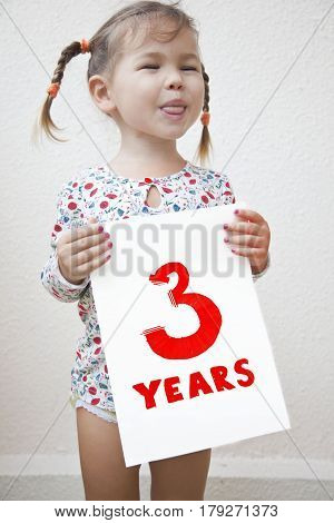 The child was three years old a girl holding a sign with the words