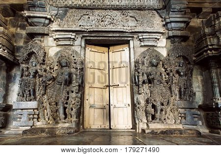 Hindu gods sculpture at entrance door to traditional style stone Hoysaleswara temple, 12th century structure, India. Temple was built in 1150 by king of Hoysala Empire now Karnataka state.
