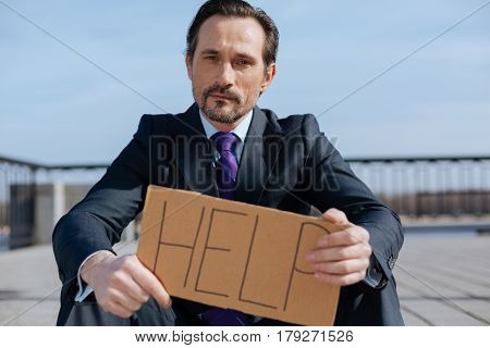 Wait for your advice. Serious man sitting on the pavement holding cardboard while looking straight on camera