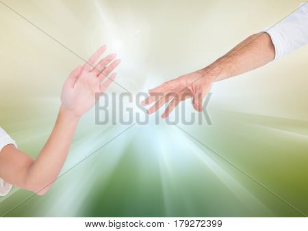 Digital composite of Hands reaching for eachother against abstract background
