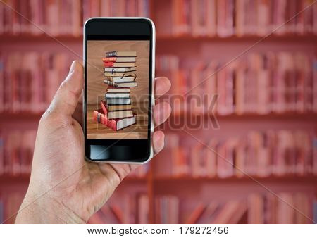 Digital composite of Hand with phone showing book pile against blurry bookshelf with red overlay