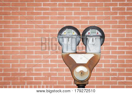 Old parking meter showing expired time with red brick wall background