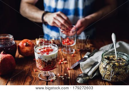 Dessert with Pomegranate and Guy Prepare New Portion on Backdrop. Series on Prepare Healthy Dessert with Pomegranate, Granola, Cream and Jam