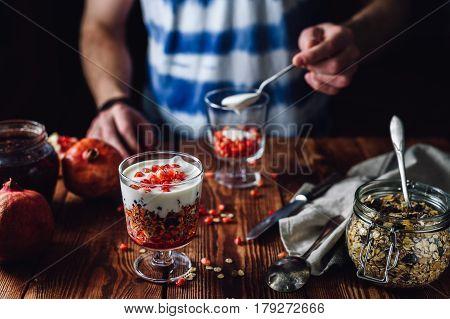 Pomegranate Dessert and Guy Prepare New Portion on Backdrop. Series on Prepare Healthy Dessert with Pomegranate, Granola, Cream and Jam
