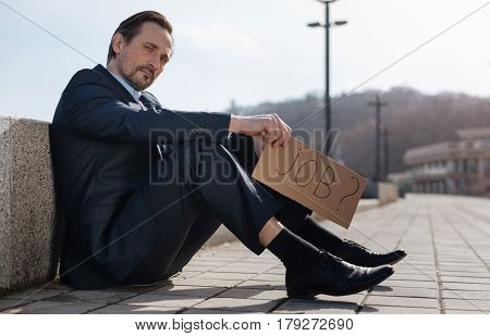 Watch me. Attractive smart man holding cardboard in right hand while posing at camera sitting in semi position