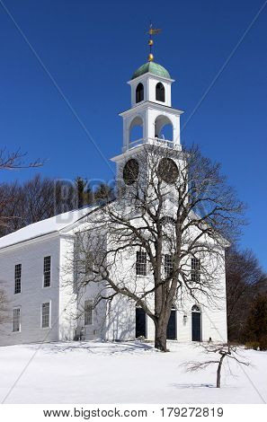 A white clapboard New England church on a snowy day in winter
