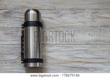 Metal thermos flask on a woden background.
