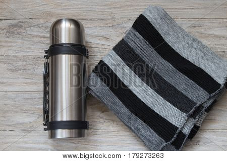 Metal thermos flask on a woden background. Top view