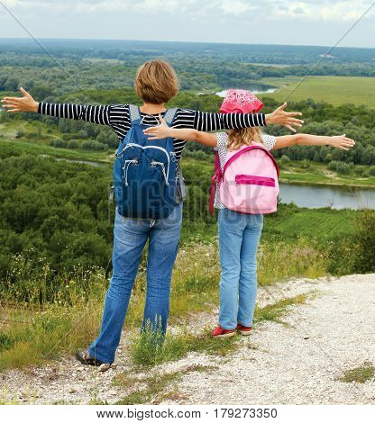 Adult and child standing on a mountaintop near river. Family hiking in mountains on vacation