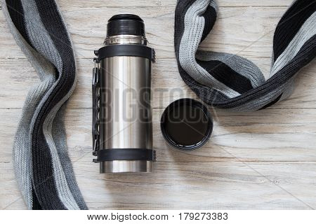 Thermos flask made of stainless steel on a woden background. Top view