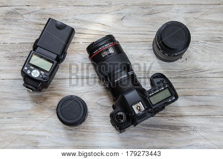 Camera and camera lens well organized over wooden background. Top view