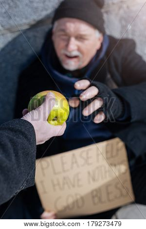 Give it to me. Young male hand holding green apple than giving it to needy man who sitting in the street