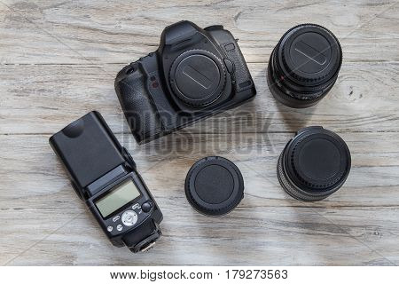 Camera and camera lens on a wooden background. Top view