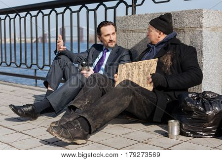 Understand me. Poor man being in dirty clothes sitting near garbage bag while listening to passersby