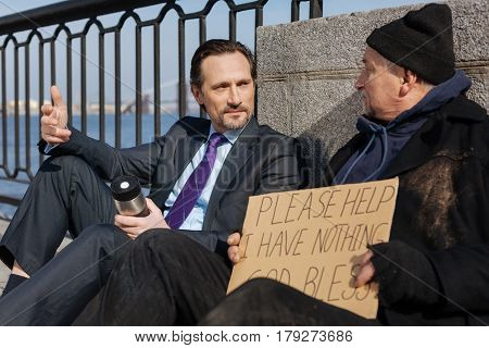 Use gesticulation. Confident bearded man holding thermos in left hand wearing costume, speaking with homeless