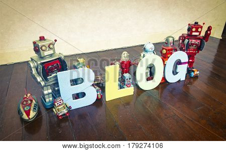 the word   BLOG on wooden floor with reto robots