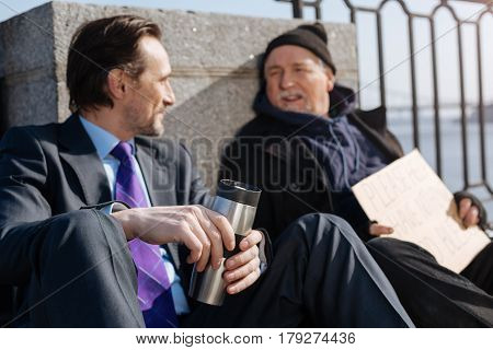 We can change our life. Young handsome man wearing new costume putting left arm on the knee, holding thermos in his hands