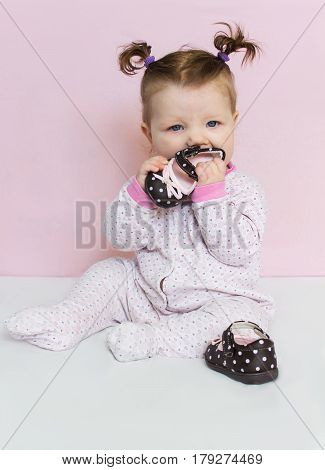 Beautiful little an infant girl sits and plays with children's shoes. A child with long braided hair.