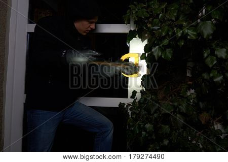 burglar trying to get into a house using a crowbar, with torchlight flare, in motion