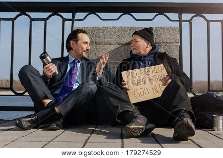Best interlocutor. Kind homeless wearing black cap and untidy coat turning his head while listening new friend
