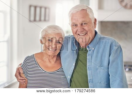 Portrait of a smilng senior man with his arm around his wife's shoulder while standing together in their  kitchen at home