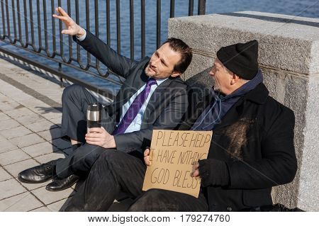 Look right here. Very attentive homeless wearing black cap and untidy coat turning his head while listening new friend